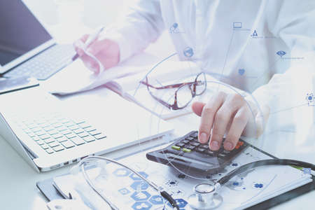 Healthcare costs and fees concept.Hand of smart doctor used a calculator for medical costs in modern hospital with VR icon diagram Banco de Imagens