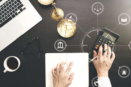 justice and law concept.businessman or lawyer or accountant working on accounts using a calculator and laptop computer and documents with Vr diagram Standard-Bild