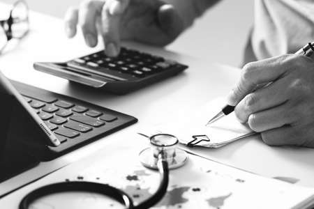 Healthcare costs and fees concept.Hand of smart doctor used a calculator for medical costs in modern hospital ,black and white Standard-Bild