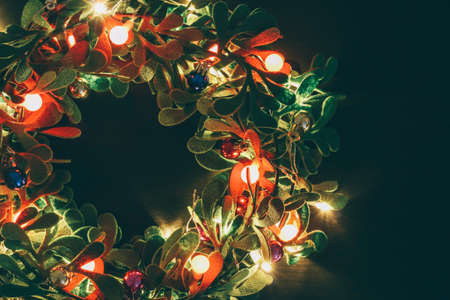 Greeting Season concept.Christmas wreath with decorative light on dark wood background Banque d'images