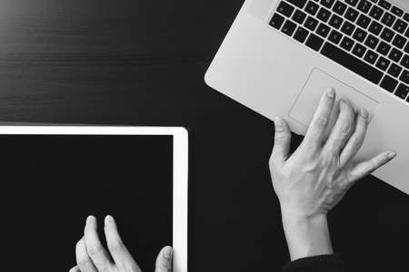 cyber security internet and networking concept.Businessman hand working with  laptop computer and digital tablet background,black and white