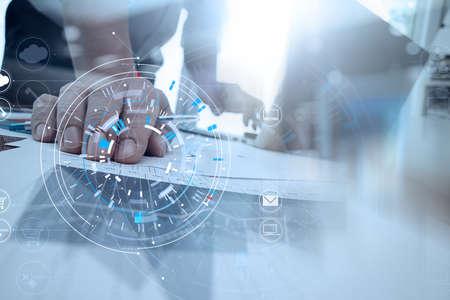 Manos del empresario usando el teléfono móvil en la oficina moderna con computadora portátil y tableta digital en equipo de finanzas reunidos con el diagrama del icono VR Foto de archivo