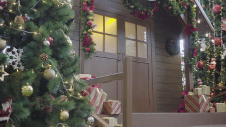 Greeting Season concept. Gimbal shot of ornaments on Christmas tree with decorative light and front home with door