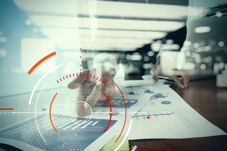 Concept of target focus digital diagram,graph interfaces,virtual UI screen,connections netwoork.Businessman working with laptop computer and finance document at modern office  Standard-Bild