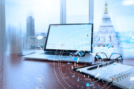 Office workplace with laptop and smart phone on wood table and london city blurred background with VR diagram Standard-Bild