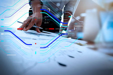 Concept of focus on target with digital diagram.business documents on office table with smart phone and laptop computer and graph business with social network diagram and man working in the background Stock Photo
