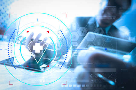 Health care and medical services with circular AR diagram.Medical technology network team meeting concept. Happy Doctor hand working smart phone keyboard docking digital tablet screen laptop computer. Stock Photo
