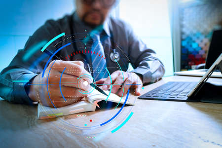 Health care and medical services with circular AR diagram record.medical doctor writing on notebook and digital tablet docking keyboard with laptop. Stock Photo