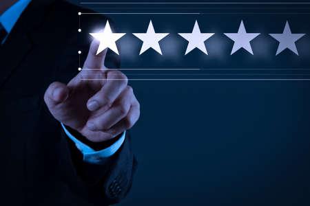 Die Bewertung mit fünf Sternen (5) bei einem Geschäftsmann berührt den Bildschirm des virtuellen Computers. Für positives Kundenfeedback und Bewertung mit hervorragender Leistung.