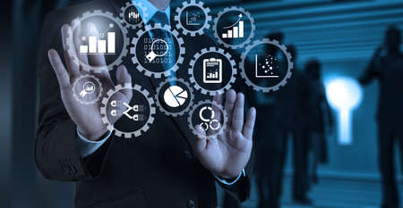 Business data analytics management with connected gear cogs with KPI financial charts and graph.Businessman hand pressing an imaginary button on virtual screen