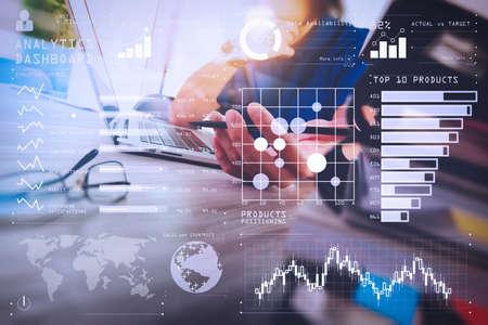 Intelligence (BI) et analyse commerciale (BA) avec concept de tableau de bord d'indicateurs de performance clés (KPI) .Designer travaillant à la main avec une tablette numérique et un ordinateur portable et une pile de livres et un verre oculaire sur un bureau en bois.