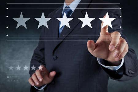 La calificación de cinco estrellas (5) con un empresario es tocar la pantalla de la computadora virtual. Para comentarios positivos de los clientes y revisión con excelente rendimiento. Foto de archivo
