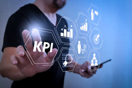 Key Performance Indicator (KPI) workinng with Business Intelligence (BI) metrics to measure achievement and planned target.Designer hand pressing an imaginary button,holding smart phone.