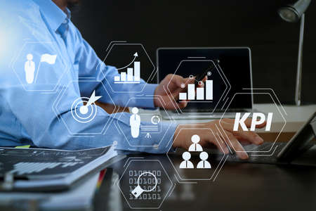 Key Performance Indicator (KPI) workinng with Business Intelligence (BI) metrics to measure achievement and planned target.businessman working with smart phone and digital tablet and laptop computer in modern office Archivio Fotografico - 101274170