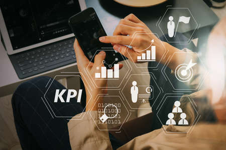 Key Performance Indicator (KPI) workinng with Business Intelligence (BI) metrics to measure achievement and planned target.hand using smart phone and digital tablet computer for online banking payment communication.