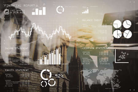 Financial report data of business operations (balance sheet and income statement and diagram) as Fintech concept.Double exposure of success businessman hand using smart phone and digital tablet.