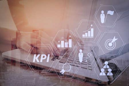 Key Performance Indicator (KPI) che lavora con le metriche di Business Intelligence (BI) per misurare il raggiungimento e l'obiettivo pianificato. Uomo d'affari che lavora con il computer portatile sulla scrivania di legno in un ufficio moderno.