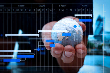Project manager working and update tasks with milestones progress planning and Gantt chart scheduling diagram.businessman hand showing texture the world. Stock Photo