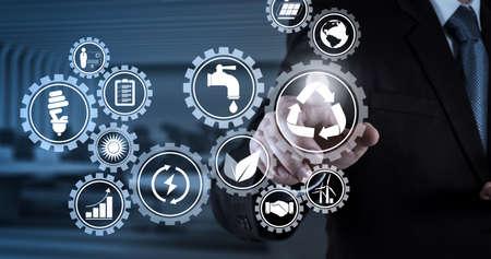 Desarrollo sostenible con iconos de energía renovable y preservación de recursos naturales con protección del medio ambiente dentro de engranajes conectados Mano de empresario presionando un botón imaginario en la pantalla virtual