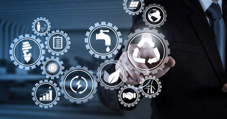 Sustainable development with icons of renewable energy and natural resources preservation with environment protection inside connected gears.Businessman hand pressing an imaginary button on virtual screen