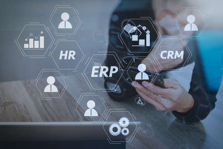 Architecture of ERP (Enterprise Resource Planning) system with connections between business intelligence (BI), production, CRM modules and HR diagram.Businessman hand using mobile payments online shopping. Stock Photo