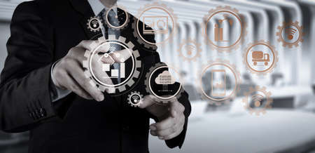 Smart factory and industry 4.0 and connected production robots exchanging data with internet of things (IoT) with cloud computing technology.Businessman hand pressing an imaginary button on virtual screen Banque d'images