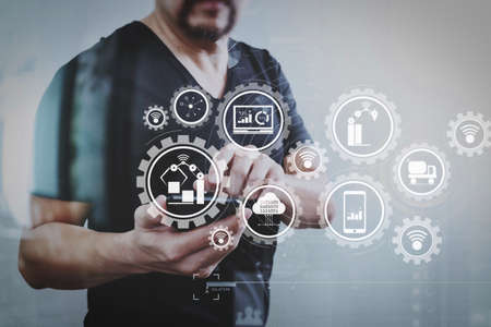 Smart factory and industry 4.0 and connected production robots exchanging data with internet of things (IoT) with cloud computing technology.Designer hand using smart phone for mobile payments online. Stock Photo