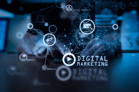 Digital marketing media (website ad, email, social network, SEO, video, mobile app) in virtual screen.Businessman hand using mobile phone with digital layer effect as business strategy concept.                  Stockfoto