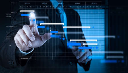 Project manager working and update tasks with milestones progress planning and Gantt chart scheduling diagram.businessman hand working with touch screen in action. Stock Photo
