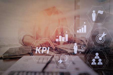 Key Performance Indicator (KPI) che lavora con metriche di Business Intelligence (BI) per misurare il raggiungimento e l'obiettivo pianificato. Uomo d'affari che lavora con smartphone e computer portatile sulla scrivania di legno.
