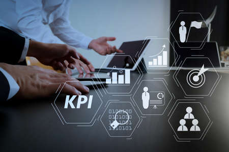 Key Performance Indicator (KPI) workinng with Business Intelligence (BI) metrics to measure achievement and planned target.co working team meeting concept,businessman using smart phone and digital tablet and laptop computer. Archivio Fotografico - 101657821