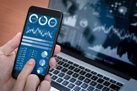 Investor analyzing stock market report and financial dashboard with business intelligence (BI), with key performance indicators (KPI).Businessman using smart phone with laptop computer.