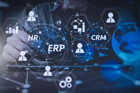 Architecture of ERP (Enterprise Resource Planning) system with connections between business intelligence (BI), production, CRM modules and HR diagram.businessman hand working with modern digital tablet computer. Stock Photo