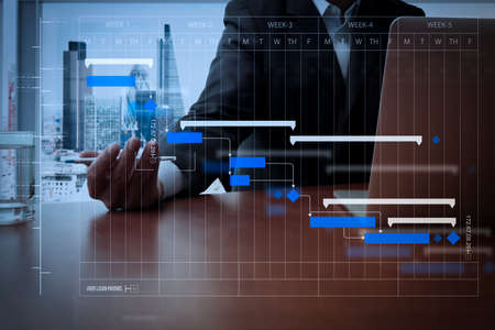 Project manager working and update tasks with milestones progress planning and Gantt chart scheduling diagram.business documents on office table with smart phone and digital tablet and graph.