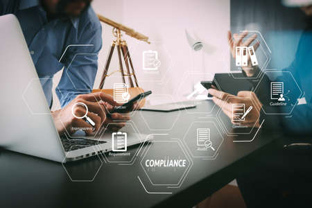 Compliance Virtual Diagram for regulations, law, standards, requirements and audit.co working team meeting concept,businessman using smart phone and digital tablet and laptop computer in modern office                                Stock Photo