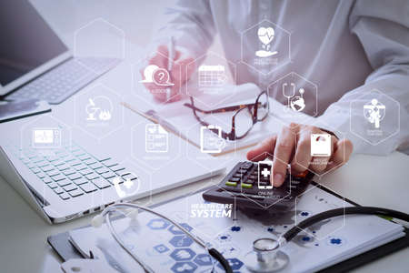 Health care system diagram with health check and symptom on VR dashboard.Healthcare costs and fees concept.Hand of smart doctor used a calculator for medical costs in modern hospital Stock Photo