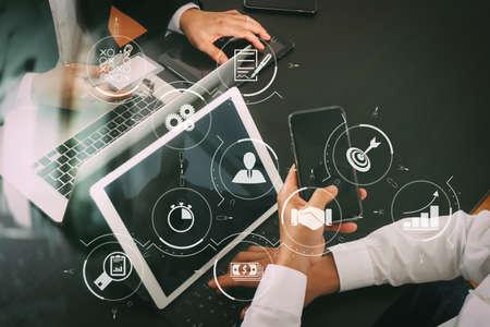 Zarządzanie procesami biznesowymi z diagramem automatyzacji przepływu pracy i biegami w wirtualnym schemacie blokowym. Koncepcja spotkania zespołu roboczego, biznesmen za pomocą smartfona i cyfrowego tabletu i laptopa oraz plakietki. Zdjęcie Seryjne