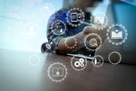 E-learning z połączonymi zębatkami połączonymi z wirtualnym pulpitem nawigacyjnym. Ręka biznesmena pracująca na laptopie ze schematem mediów społecznościowych na drewnianym biurku Zdjęcie Seryjne