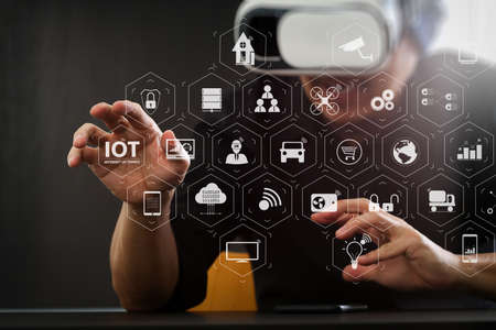 Internet of Things (IOT) technology with AR (Augmented Reality) on VR dashboard. businessman wearing virtual reality goggles in modern office with Smartphone using with VR headset with screen icon diagram Archivio Fotografico