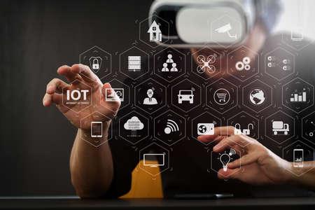 Tecnologia Internet of Things (IOT) con AR (Augmented Reality) su dashboard VR. uomo d'affari che indossa occhiali per realtà virtuale in ufficio moderno con Smartphone utilizzando con auricolare Vr con diagramma icona schermo