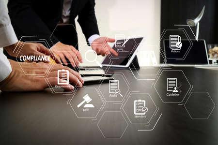 Wirtualny diagram zgodności dla przepisów, prawa, norm, wymagań i audytu. Koncepcja spotkania zespołu roboczego co, biznesmen za pomocą smartfona i cyfrowego tabletu i laptopa w nowoczesnym biurze