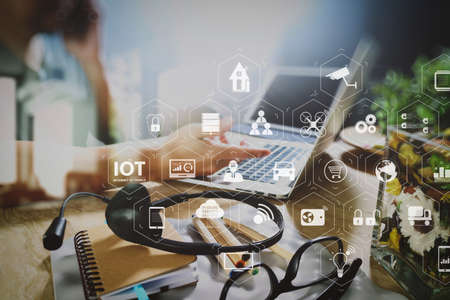 Internet of Things (IOT) technology with AR (Augmented Reality) on VR dashboard. Man using VOIP headset with digital tablet computer docking smart keyboard, concept communication, it support, call center