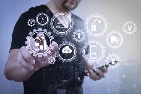 スマートファクトリーとインダストリー4.0、クラウドコンピューティング技術でモノのインターネット(IoT)とデータを交換するコネクテッドプロダクションロボット。ビジネスマンの手は、スマートフォンを保持し、想像上のボタンを押して。 写真素材 - 103386209