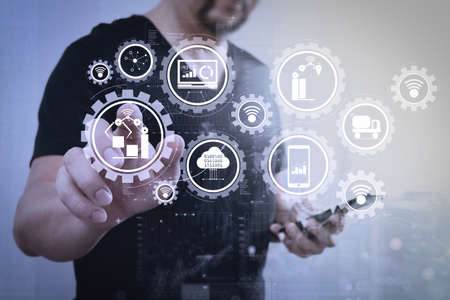 Smart factory and industry 4.0 and connected production robots exchanging data with internet of things (IoT) with cloud computing technology.Businessman hand pressing an imaginary button,holding smart phone. Banque d'images