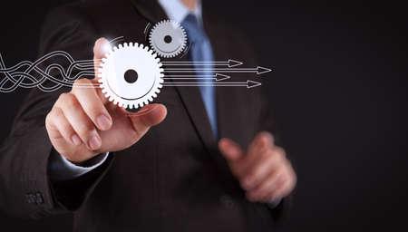 Pensando en estructurar diagrama virtual de procesos de negocio con soluciones. Mano de empresario presionando un botón imaginario en la pantalla virtual