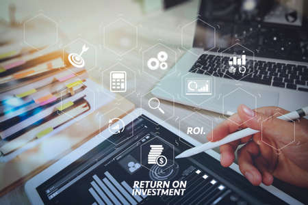 ROI Return on Investment indicator in virtual dashboard for improving business. Website designer working digital tablet and computer laptop with smart phone and digital design diagram and stack of books on wooden desk