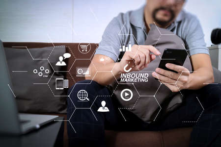 Inbound marketing business with virtual diagram dashboard and Online or permission market concept.hipster hand using digital tablet docking keyboard and smart phone for mobile payments online business.
