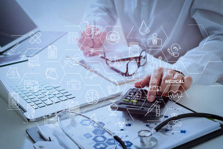 Health care and medical services concept with flat line AR interface.Healthcare costs and fees concept.Hand of smart doctor used a calculator for medical costs in modern hospital