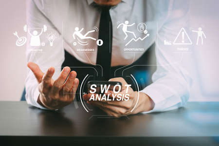 SWOT Analysis virtual diagram with Strengths, weaknesses, threats and opportunities of company. businessman working with smart phone on wooden desk in modern office with glass reflected view Reklamní fotografie