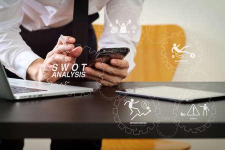 Diagrama virtual de análisis FODA con fortalezas, debilidades, amenazas y oportunidades de la empresa.Empresario que trabaja con teléfonos inteligentes y tabletas digitales y computadoras portátiles en un escritorio de madera en la oficina moderna Foto de archivo